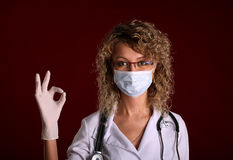 Young doctor woman with stethoscope shows ok Stock Images