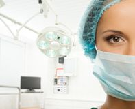 Young doctor woman in surgery room. Young woman doctor in cap and face mask in surgery room interior Stock Photo