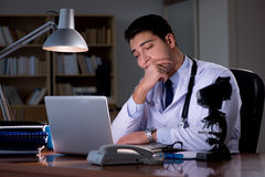 The young doctor working late in the office Stock Images