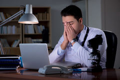 The young doctor working late in the office Royalty Free Stock Photo