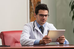 Young Doctor Working On Touchpad In Office Stock Photo