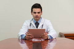 Young Doctor Working On Touchpad In Office Royalty Free Stock Image