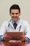 Young Doctor Working On Touchpad In Office Stock Photography