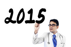 Young doctor writes number 2015 on whiteboard Royalty Free Stock Image