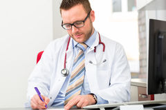 Young doctor writing medical prescription Stock Photos