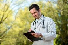 Young doctor writing recipe with stethoscope Royalty Free Stock Photos