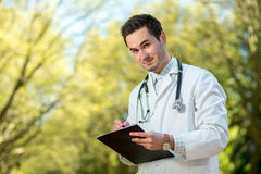 Young doctor writing recipe with stethoscope Stock Images