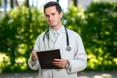 Young doctor writing recipe Royalty Free Stock Images