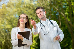 Young doctor with young and pretty assistan Royalty Free Stock Images