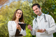 Young doctor with young and pretty assistant speaking Stock Photo