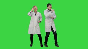 Young doctors in a good mood dancing and singing songs on a Green Screen, Chroma Key.