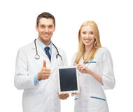 Young doctors holding tablet pc in hands. Two young doctors holding tablet pc in hands Royalty Free Stock Image