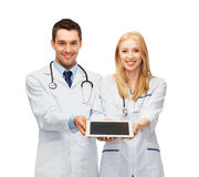 Young doctors showing tablet pc. Two young doctors holding tablet pc in hands Stock Photo