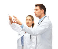 Young doctors working with something imaginary. Healthcare, medical and technology concept - two young doctors working with something imaginary Stock Images