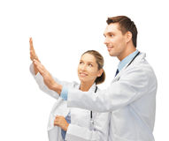 Young doctors working with something imaginary. Two young doctors working with something imaginary Stock Photography
