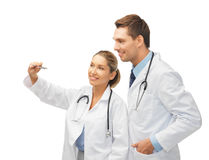 Young doctors working with something imaginary. Two young doctors working with something imaginary Royalty Free Stock Photography