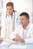 Young doctors working together in office. Young attractive doctors working together in bright office royalty free stock images