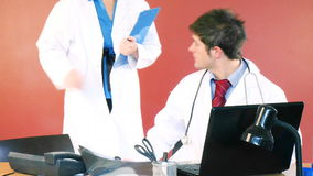Young doctors working together in office. Beautiful female doctor coming into an office where a handsome male doctor is working with a laptop footage stock video