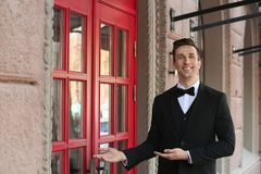 Young doorman in elegant suit standing near restaurant. Entrance royalty free stock images