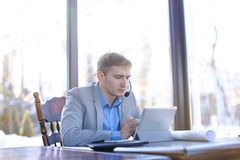 Young draftsman talking with client by tablet, headset phones an. Hardworking tired draftsman talking by tablet with engineer about project at cafe. Young man stock photos