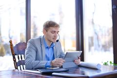 Young draftsman talking with client by tablet, headset phones an. Hardworking tired draftsman talking by tablet with engineer about project at cafe. Young man royalty free stock photos