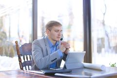 Young draftsman talking with client by tablet, headset phones an. Hardworking tired draftsman talking by tablet with engineer about project at cafe. Young man royalty free stock photography