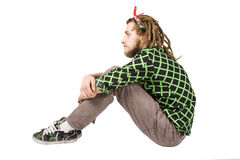 Young dreadlock man sits isolated Stock Photo