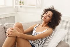 Young dreaming black woman sitting on couch royalty free stock photos