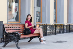 Young dreaming female holding cell telephone while sitting on bench in the fresh air, attractive brunette woman chatting on her sm Stock Image