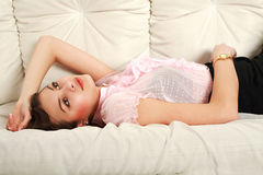 Young dreaming girl, lying on white sofa Royalty Free Stock Image
