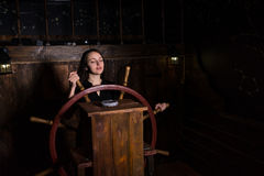 A young dreaming girl stands at the helm of the ship. Escape the room game concept stock photography