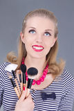 Young dreaming pinup woman with make up brushes Stock Images