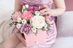 Young dreaming woman holding Square Pink Flower box with Fresh Rose and candies.  Royalty Free Stock Photo