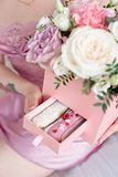 Young dreaming woman holding Square Pink Flower box with Fresh Rose and candies.  Royalty Free Stock Image