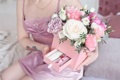 Young dreaming woman holding Square Pink Flower box with Fresh Rose and candies.  Royalty Free Stock Images
