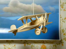 Young Dreams of Flying. A simple wooden model of a World War One fighter plane - hanging on a string in front of a photograph of clouds Royalty Free Stock Photography