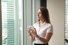 Young dreamy beautiful businesswoman looking through window whil Stock Photos