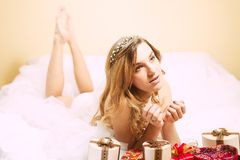 Young dreamy blonde female lying on bed with gift Stock Photography