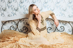 Young dreamy blonde woman in vintage hippie dress sitting on the bed Royalty Free Stock Photography