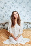 Young dreamy brunette woman in vintage lace dress sitting on the bed Stock Images