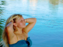 Young dreamy girl near a blue river. Royalty Free Stock Image