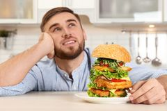 Young dreamy man holding plate with huge burger. On table stock image