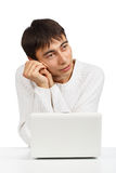 Young dreamy man sitting at the netbook Stock Photos