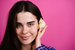 Young dreamy smiling woman listening to a shell royalty free stock photography