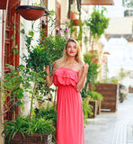 Young dreamy woman in dress walking on streets of tourist town Stock Photography
