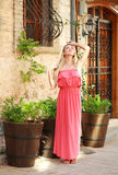 Young dreamy woman in dress walking on streets of tourist town Royalty Free Stock Images