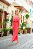 Young dreamy woman in dress walking on streets of tourist town Royalty Free Stock Photo