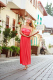 Young dreamy woman in dress walking on streets of tourist town Royalty Free Stock Photos