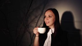 Woman with cup of coffee in dark place. Young dreamy woman enjoying coffee while standing in ray of light beside. Young dreamy woman enjoying coffee while stock footage