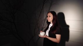 Woman with cup of coffee in dark place. Young dreamy woman enjoying coffee while standing in ray of light beside. Young dreamy woman enjoying coffee while stock video footage